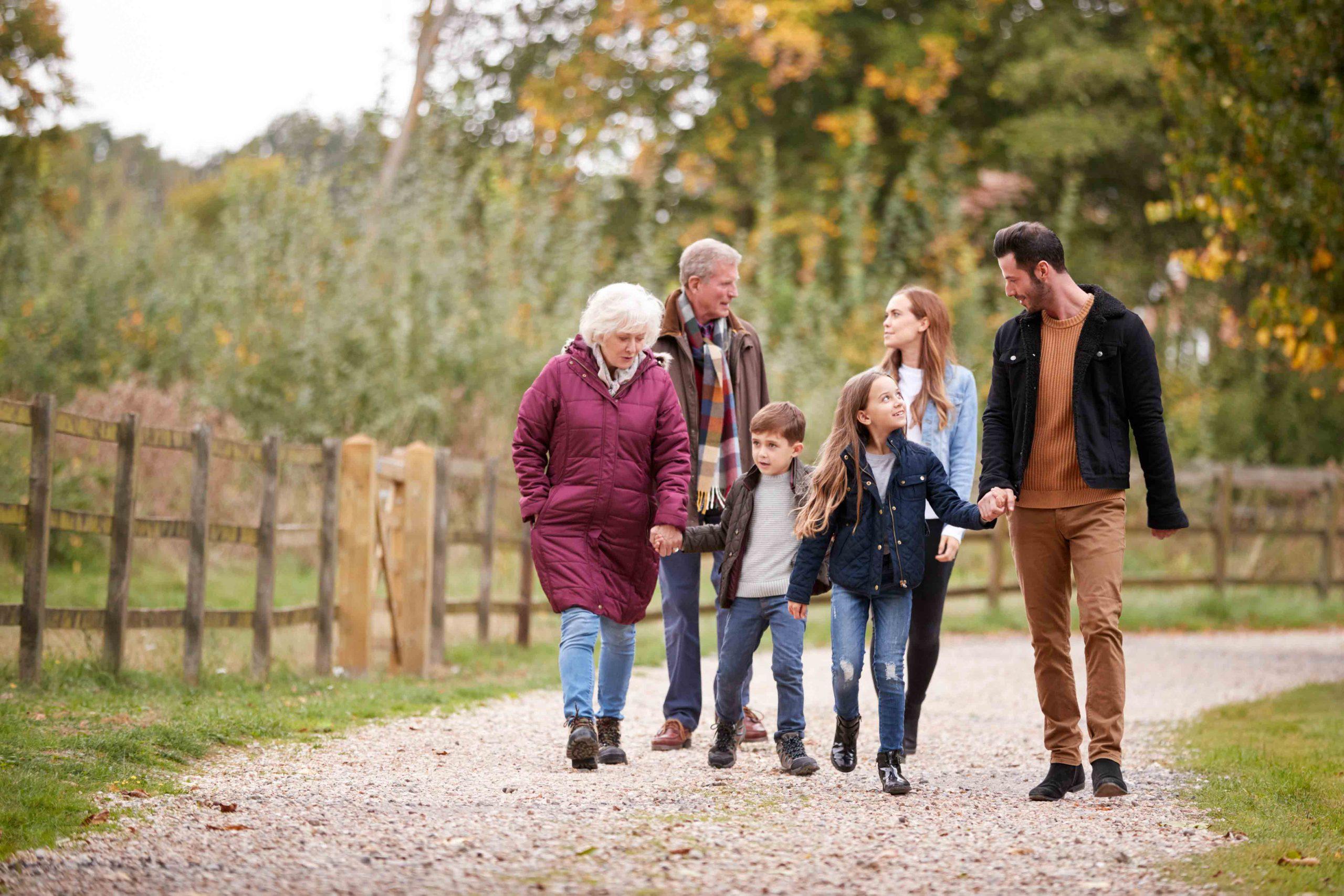 white family walking trough the fields in fall season