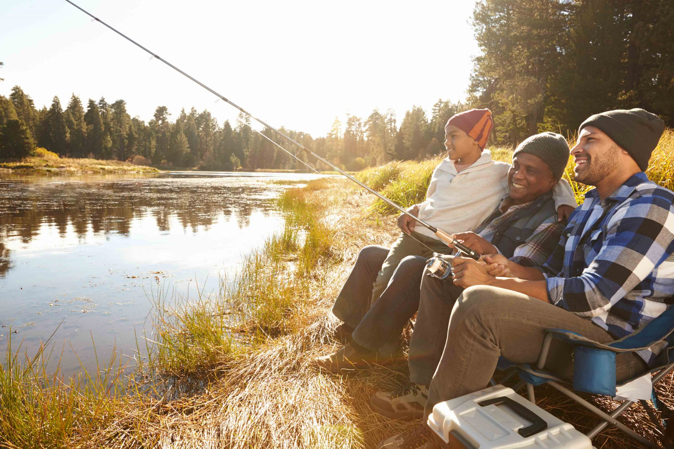 african american grandfather, father and son fishing