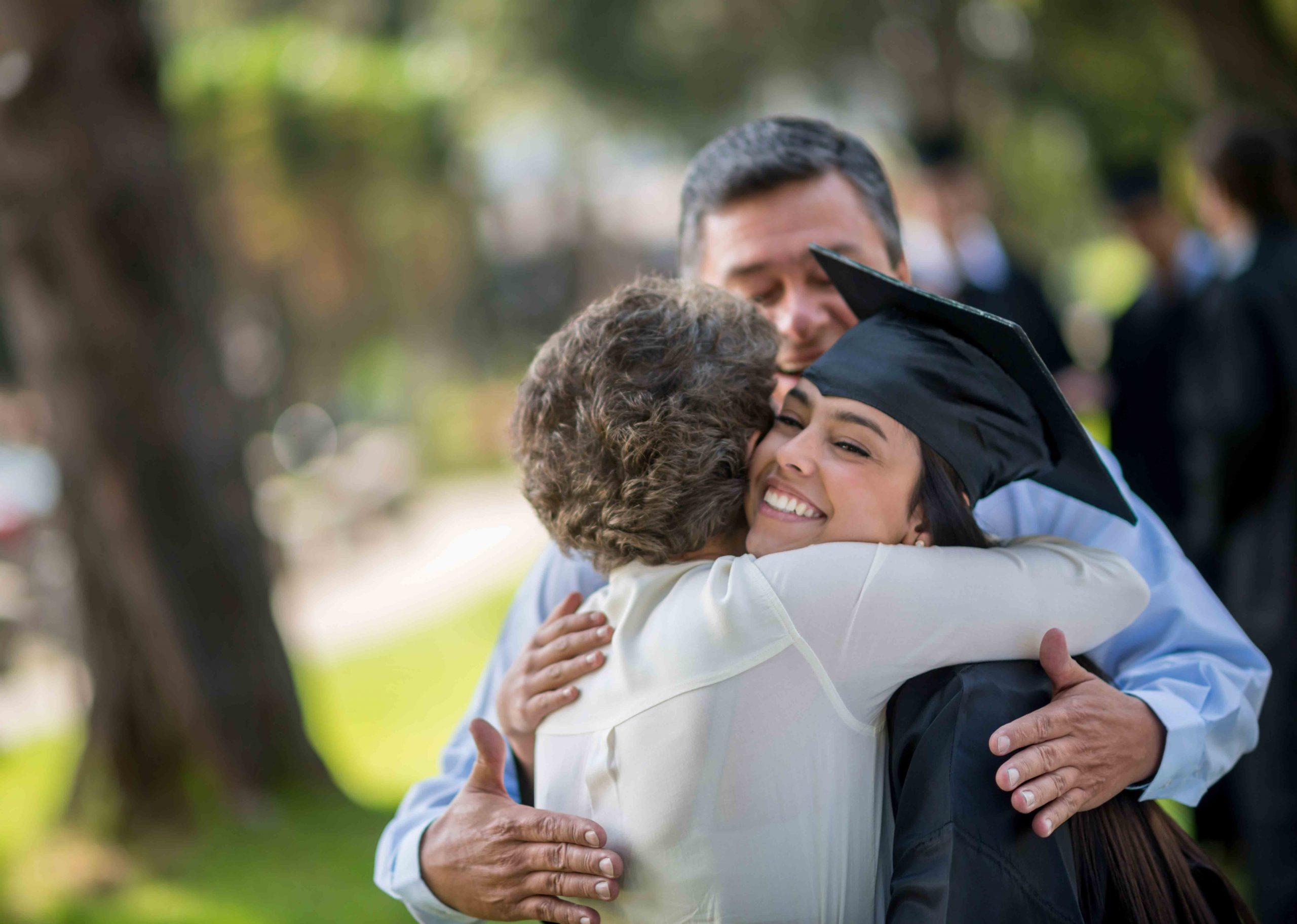 hispanic girl hugging mom after graduating